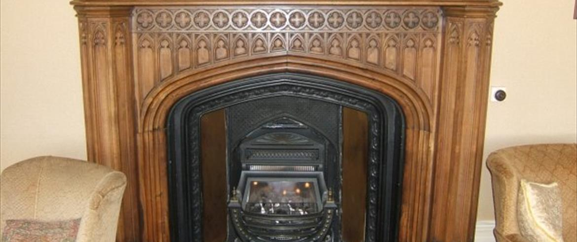 Fireplace with a carved wooden surround.  The arched opening is a four-centred arch with spandrels above containing a series of a repeated motif, representing the tall, thin arched window of a Gothic church.