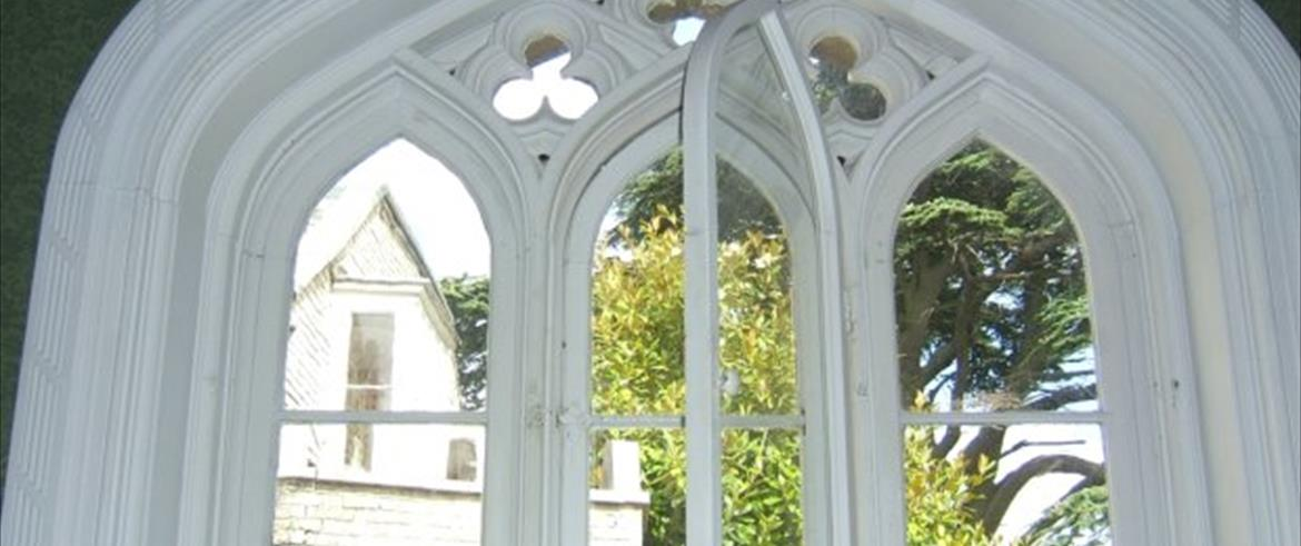 large Gothic arch window opening, containing six main lights arranged in pairs.  The bottom rectangular light comprises two rectangular panes of glass; the upper light is in a Gothic pointed arched frame, containing a rectangular pane surmounted with a pane in the shape of a pointed arch.